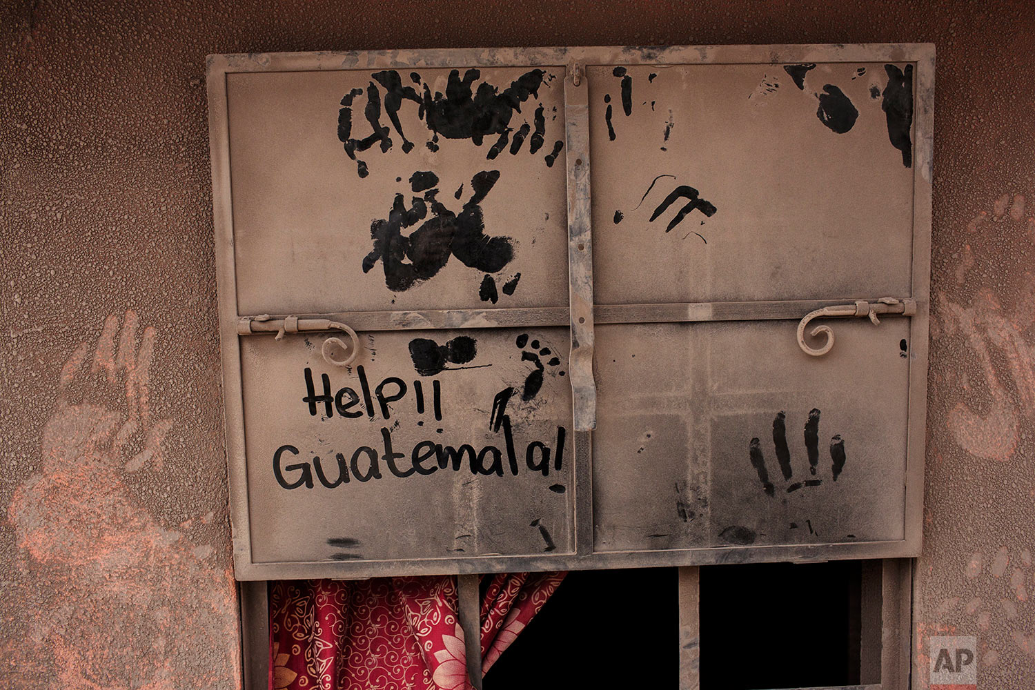 "The front door of a home blanketed in volcanic ash carries a hand written help sign in the disaster zone near the Volcan de Fuego, or ""Volcano of Fire,"" in the El Rodeo hamlet of Escuintla, Guatemala, Tuesday, June 5, 2018. (AP Photo/Rodrigo Abd)"