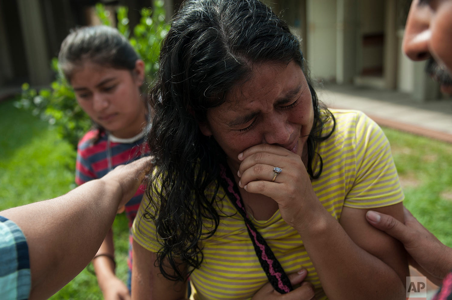 """Lilian Hernandez cries as she is comforted by her husband at the Mormon church that has been enabled as a shelter near Escuintla, Guatemala, Tuesday, June 5, 2018. Hernandez lost 36 family members in all, missing and presumed dead in the town of San Miguel Los Lotes after the fiery volcanic eruption of the Volcan de Fuego, or """"Volcano of Fire, in south-central Guatemala. (AP Photo/Oliver de Ros)"""