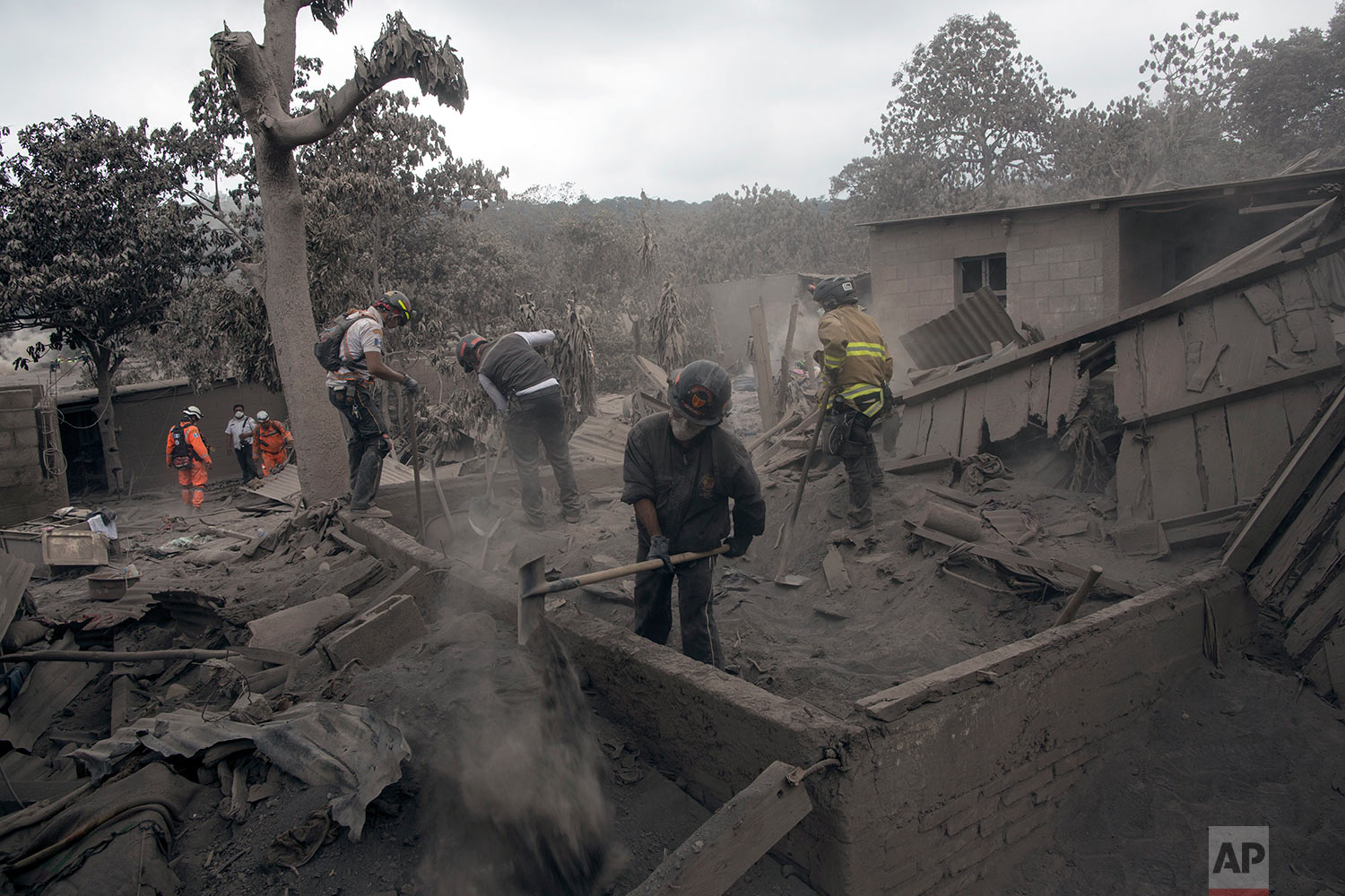 "Firefighters work in the disaster zone blanketed in volcanic ash near the Volcan de Fuego, or ""Volcano of Fire,"" in the El Rodeo hamlet of Escuintla, Guatemala, Tuesday, June 5, 2018.  (AP Photo/Rodrigo Abd)"