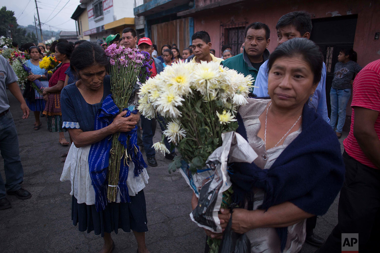 Women carry flowers during the funeral procession for seven people who died during the eruption of the Volcan de Fuego, which in Spanish means Volcano of Fire, as they make their way to the cemetery in San Juan Alotenango, Guatemala, Monday, June 4, 2018. Residents of villages skirting the volcano began mourning the dead after an eruption buried them in searing ash and mud. (AP Photo/Luis Soto)
