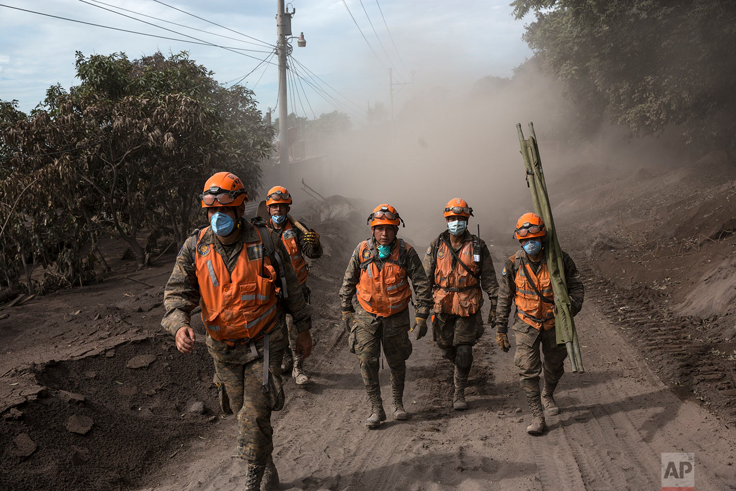 "Rescue worker walk near the Volcan de Fuego, or ""Volcano of Fire,"" in El Rodeo, Guatemala, Wednesday, June 6, 2018. Rescuers were concerned about possible dangers posed not only by more volcanic flows but also rain. Authorities have said the window is closing on the chances of finding anyone else alive in the devastation. (AP Photo/Rodrigo Abd)"