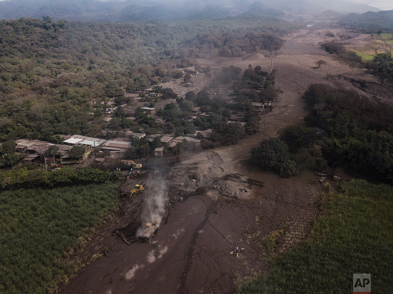 "Bulldozers work to remove volcanic ash near the Volcan de Fuego, or ""Volcano of Fire,"" in El Rodeo, Guatemala, Wednesday, June 6, 2018. Rescuers were concerned about possible dangers posed not only by more volcanic flows but also rain. Authorities have said the window is closing on the chances of finding anyone else alive in the devastation. (AP Photo/Rodrigo Abd)"