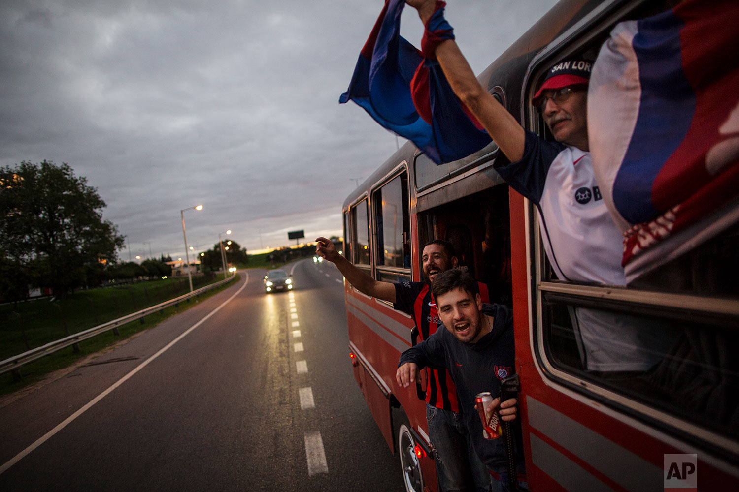 """In this April 21, 2018 photo, San Lorenzo soccer fans from the group """"Cuervos del Oeste,"""" a fan club from the outskirts of the city, sing songs and wave flags from their rental bus taking them to their team's home stadium for a game against Chacarita in Buenos Aires, Argentina. (AP Photo/Rodrigo Abd)"""