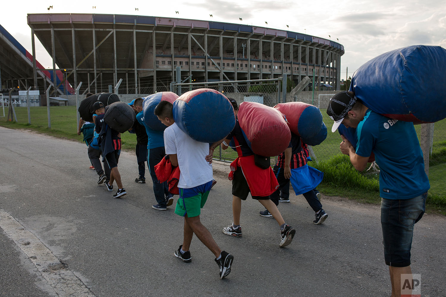 """In this April 11, 2018 photo, San Lorenzo soccer fans from the team's most militant fan base, coined """"La Butteler,"""" carry bags of team flags to be used in the stands, hours before the start of a match against Brazil's Atletico Mineiro in Buenos Aires, Argentina. (AP Photo/Rodrigo Abd)"""