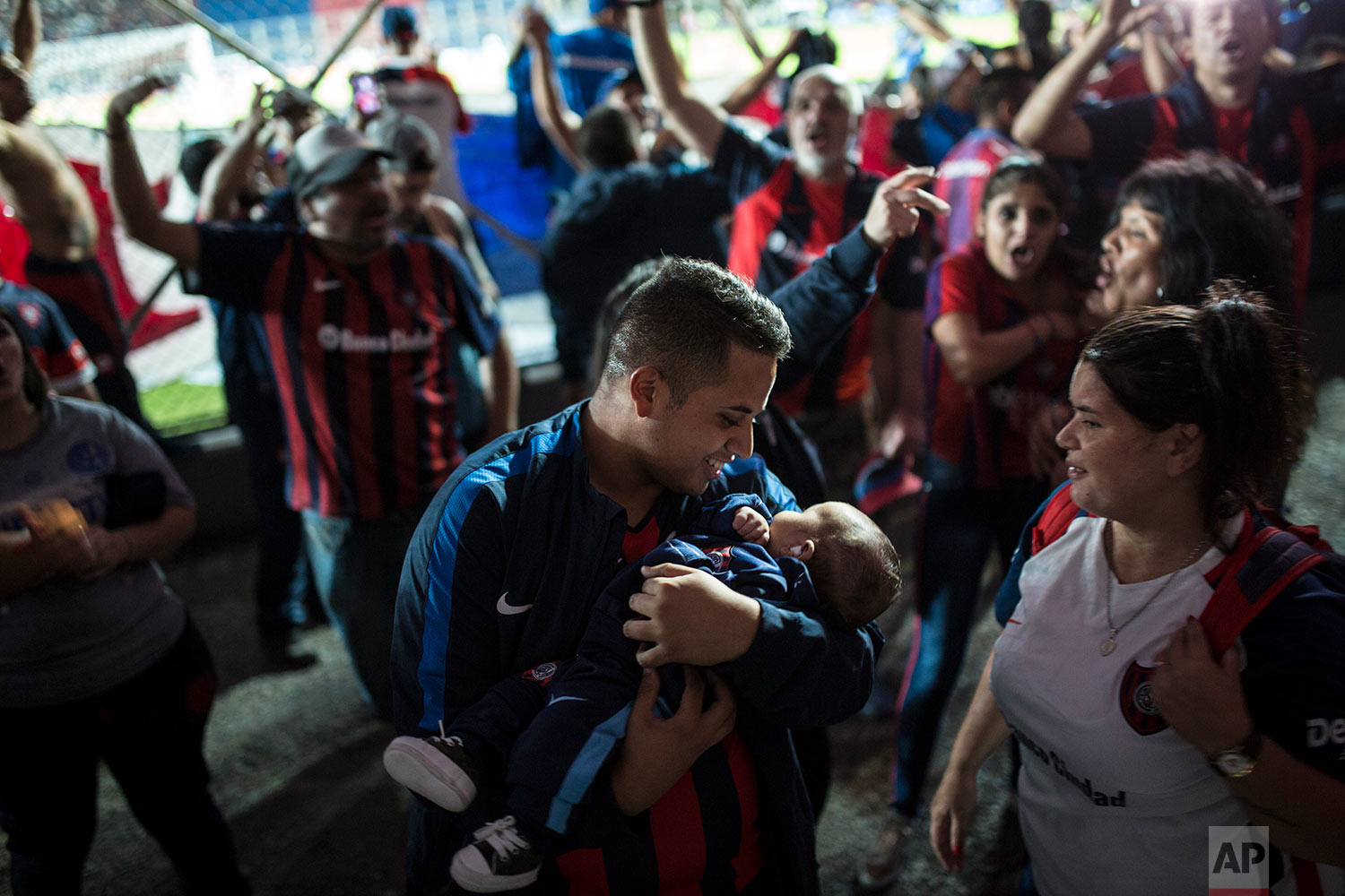 In this April 21, 2018 photo, a San Lorenzo soccer fan holds his baby amid chanting fans during a match against Chacarita in Buenos Aires, Argentina. (AP Photo/Rodrigo Abd)