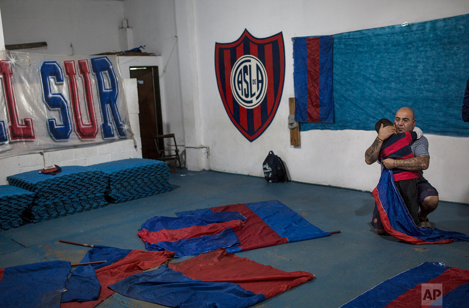 """In this April 29, 2018 photo, Fernando Mendez embraces his 4-year-old son Ilario during preparations by San Lorenzo soccer fans who call their group """"Los Cuervos del Sur"""" to watch their team play rival team Patronato on a giant screen in Buenos Aires, Argentina. (AP Photo/Rodrigo Abd)"""