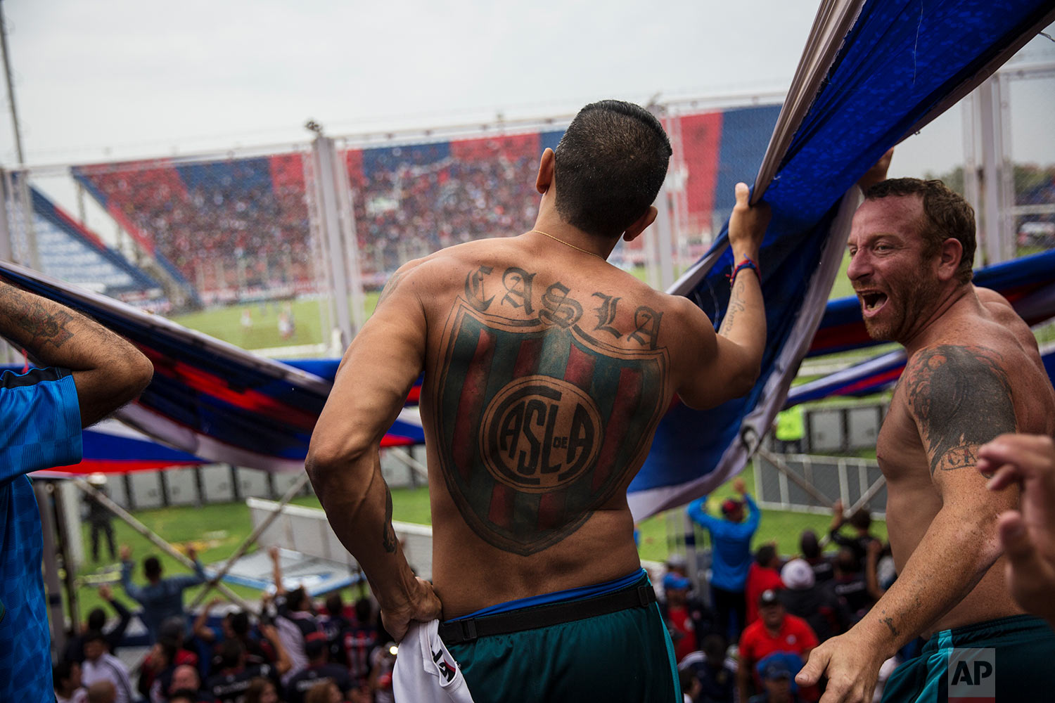 """In this April 8, 2018 photo, San Lorenzo soccer fans who are part of the team's most militant fan base, coined """"La Butteler,"""" sing and dance from the grandstand during a match against Godoy Cruz in Buenos Aires, Argentina. (AP Photo/Rodrigo Abd)"""