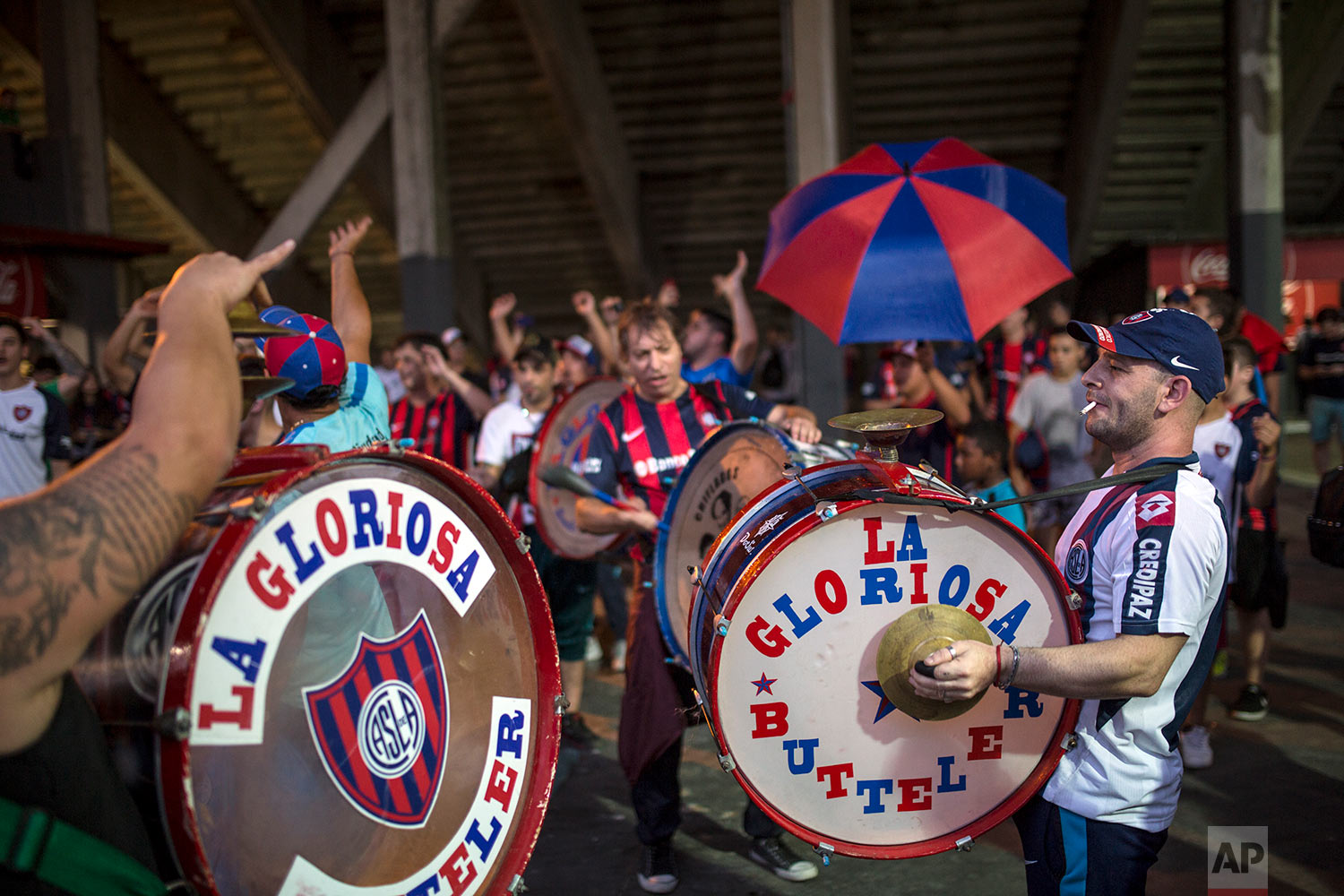 """In this April 11, 2018 photo, musicians and members of the San Lorenzo soccer team's most militant fan base, coined """"La Butteler,"""" play songs to support their team minutes before the start of a match against Godoy Cruz in Buenos Aires, Argentina. (AP Photo/Rodrigo Abd)"""