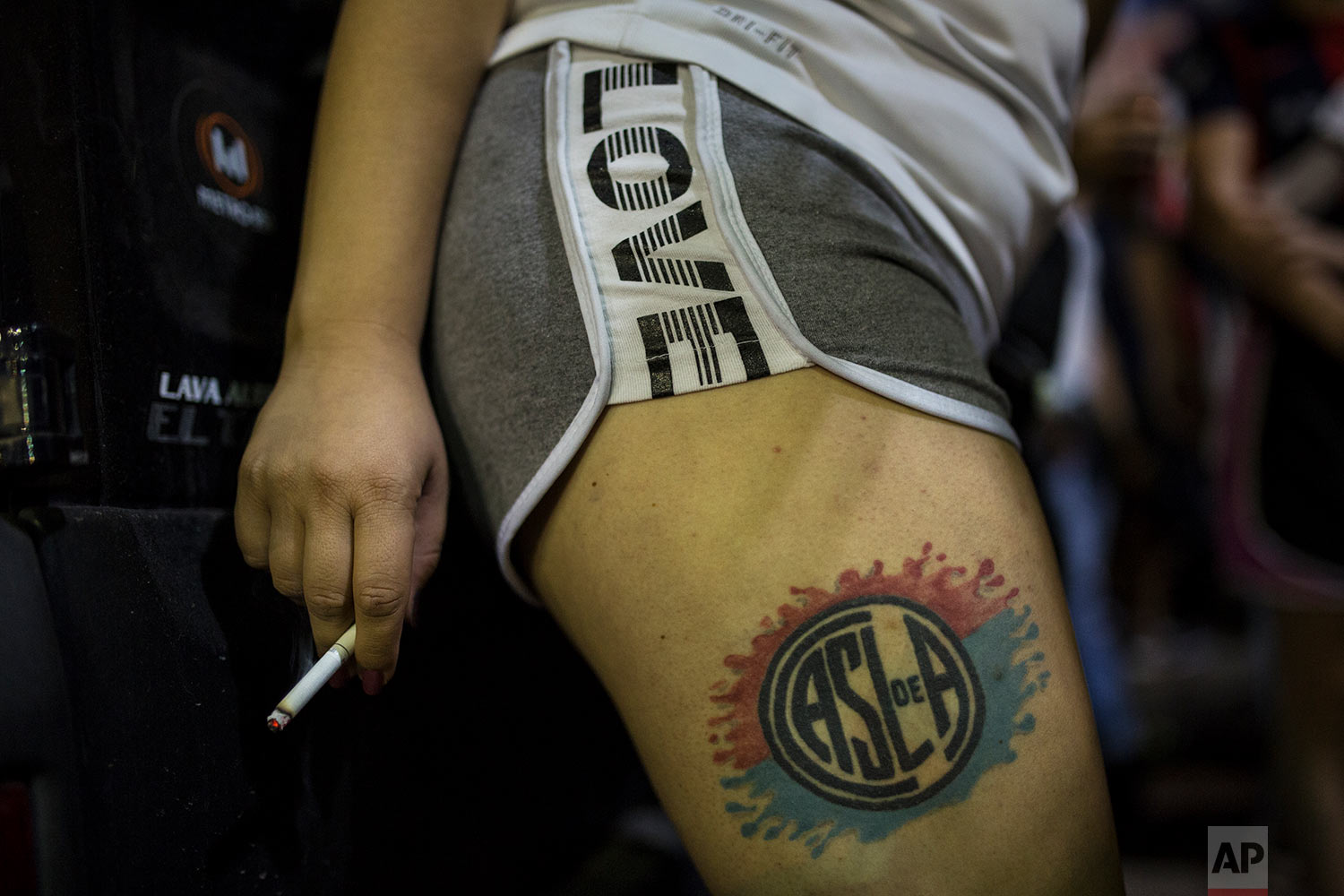 """In this April 21, 2018 photo, a woman sporting a San Lorenzo soccer team tattoo smokes a cigarette during a gathering of the """"Cuervos del Oeste"""" neighborhood fan club before a match between their team and Chacarita outside the stadium in Buenos Aires, Argentina. (AP Photo/Rodrigo Abd)"""