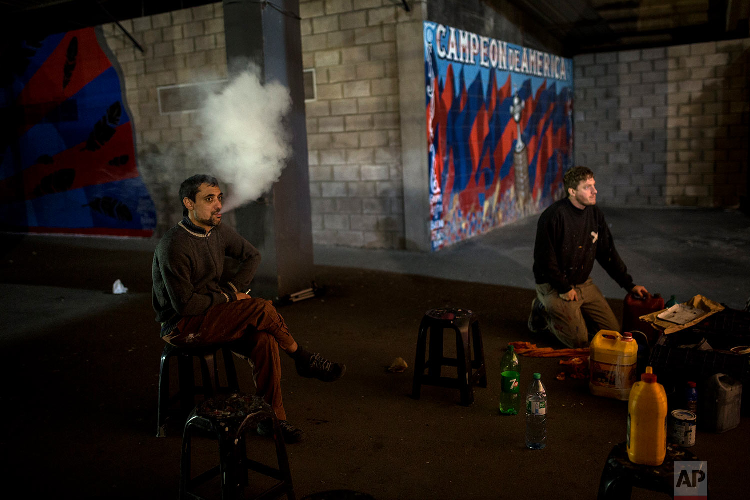 """In this April 12, 2018 photo, artists and fans of the San Lorenzo soccer team, who call themselves """"The artistic group of Boedo,"""" take a break from working on a mural inside the club's stadium in Buenos Aires, Argentina.  (AP Photo/Rodrigo Abd)"""