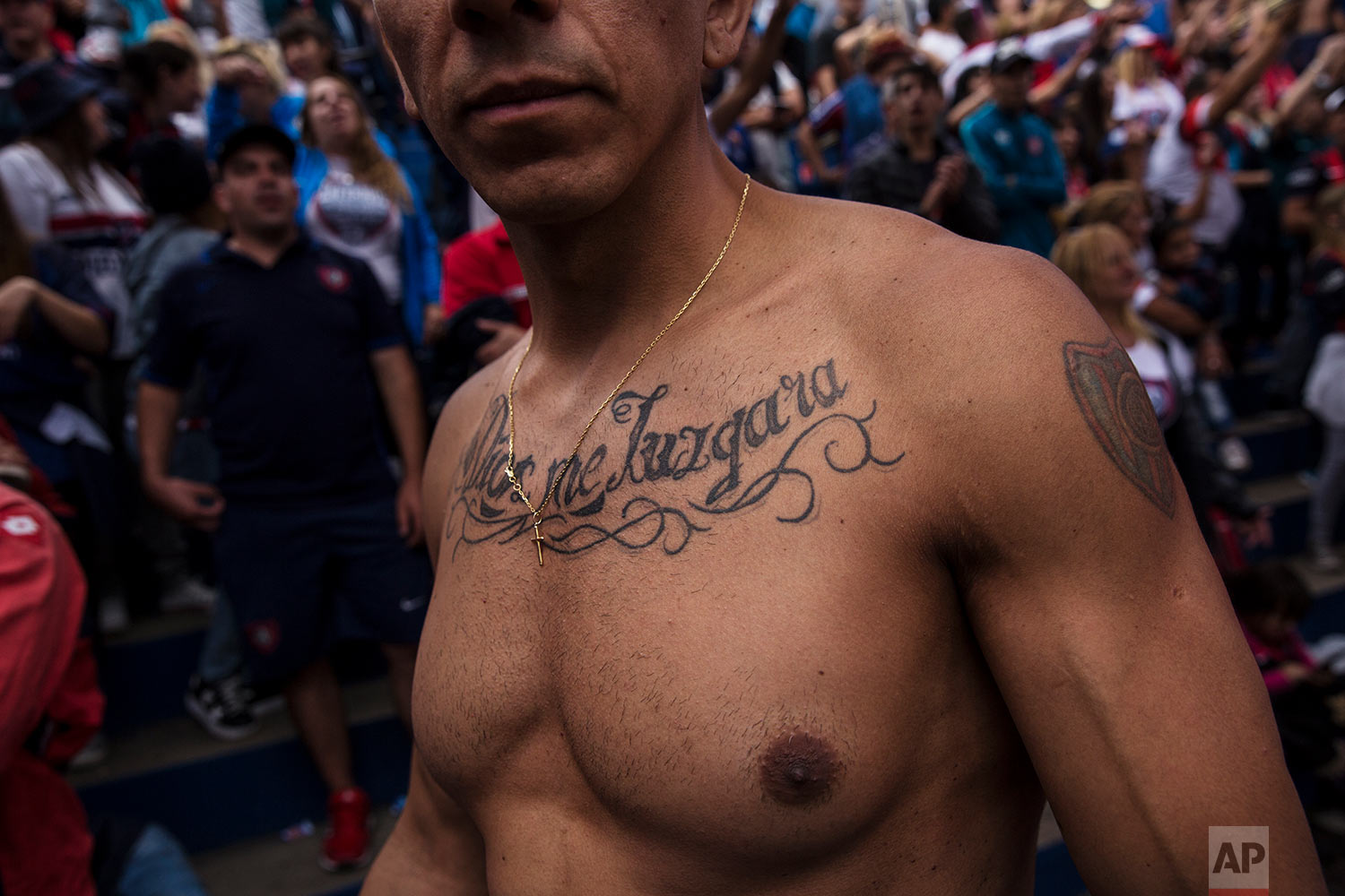 """In this April 8, 2018 photo, a San Lorenzo soccer team fan sporting a tattoo with the Spanish message: """"God will judge me"""" poses for the portrait inside the grandstand during a match against Godoy Cruz in Buenos Aires, Argentina. (AP Photo/Rodrigo Abd)"""