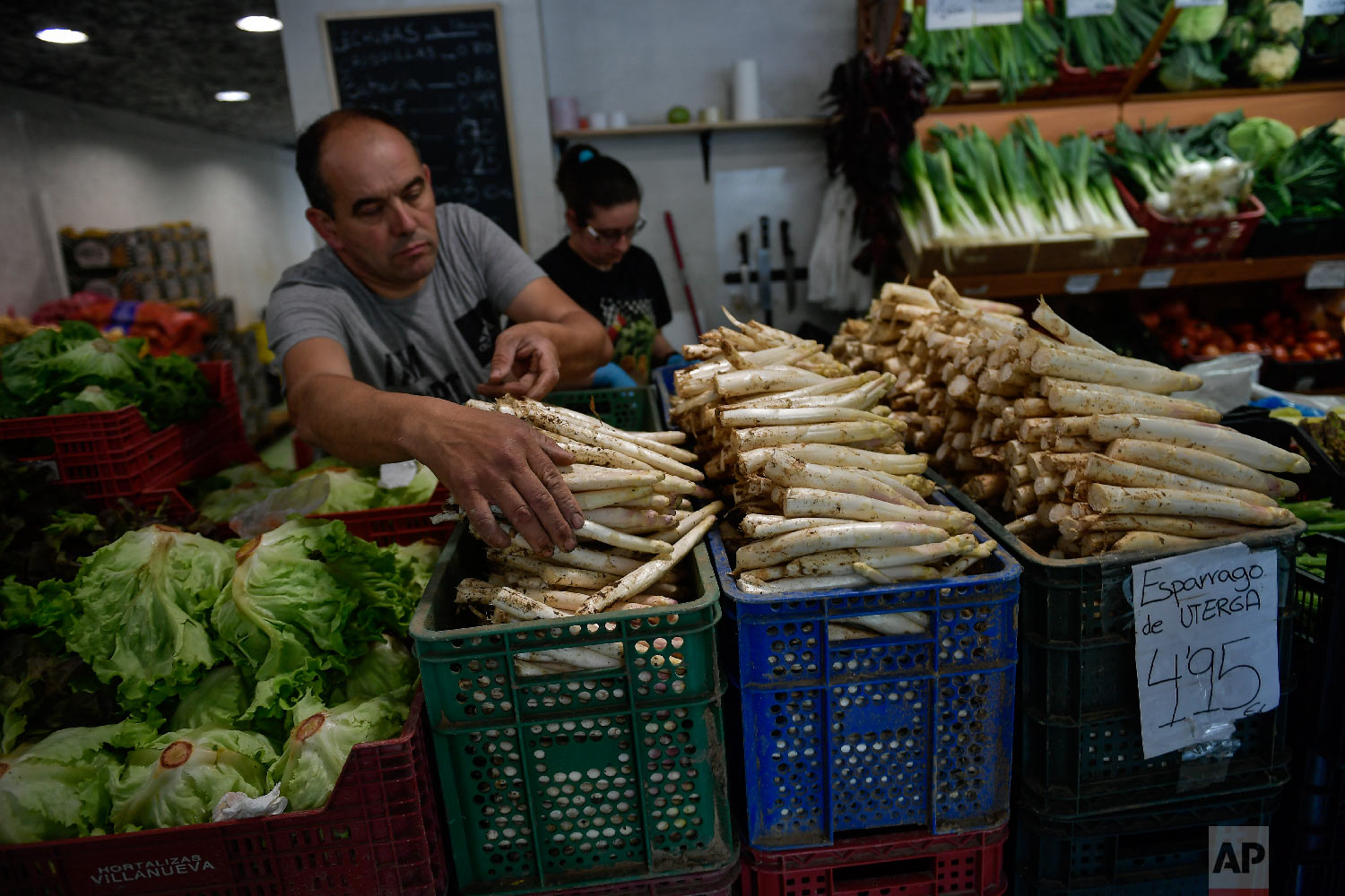 A trader organises white asparagus for customers at his store in Pamplona, northern Spain on Friday, June 1, 2018.(AP Photo/Alvaro Barrientos)