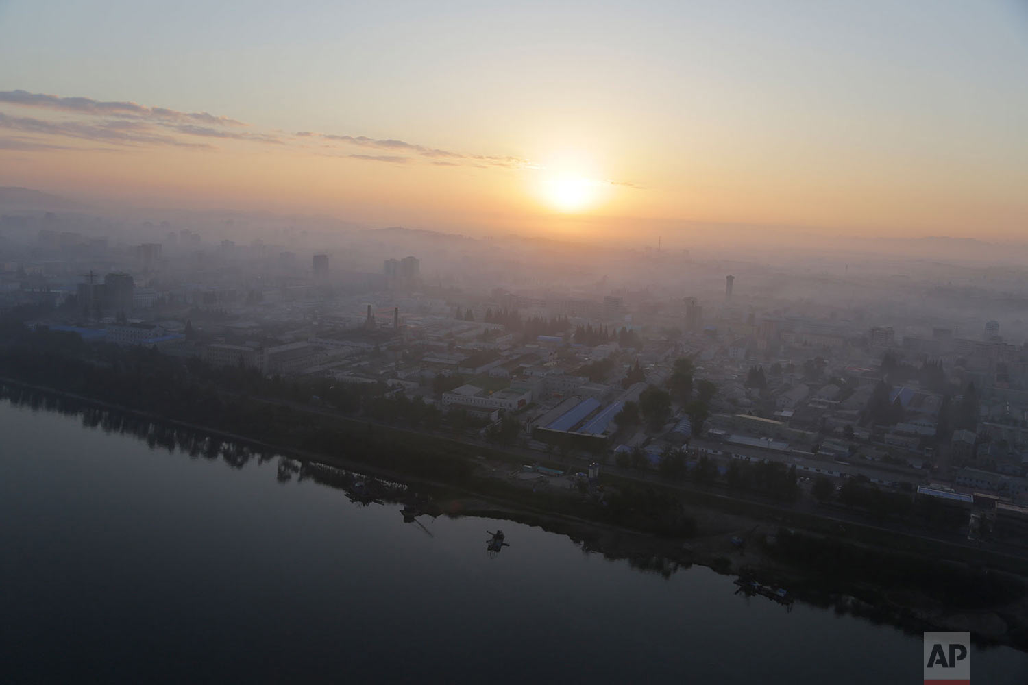 Apartment buildings peep out of the morning mist as the sun rises over Pyongyang, North Korea, on Aug. 28, 2014. (AP Photo/Wong Maye-E)