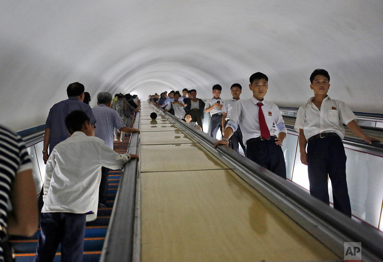 Commuters ride escalators at a subway station in Pyongyang, North Korea, on Aug. 22, 2015. (AP Photo/Dita Alangkara)