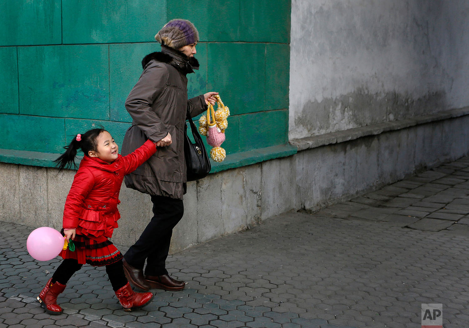 A girl walks with her mother on a downtown street in Pyongyang, North Korea, on Feb.18, 2014. (AP Photo/Vincent Yu)