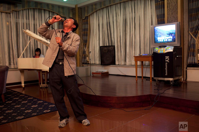 A man sings karaoke while his daughter plays piano at a hotel bar in Mount Kumgang, North Korea, on Oct. 7, 2011. (AP Photo/David Guttenfelder)