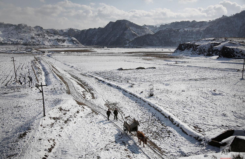 Two farmers walk between snow-covered fields on Dec. 3, 2015, in Kujang county in North Pyongan, North Korea, where the winter season has begun. (AP Photo/Wong Maye-E)