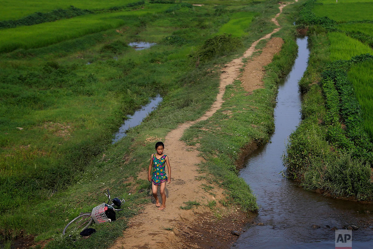 A young girl dressed in her swimming suit walks along a stream between fields in Hamju, North Korea, on July 20, 2017. (AP Photo/Wong Maye-E)