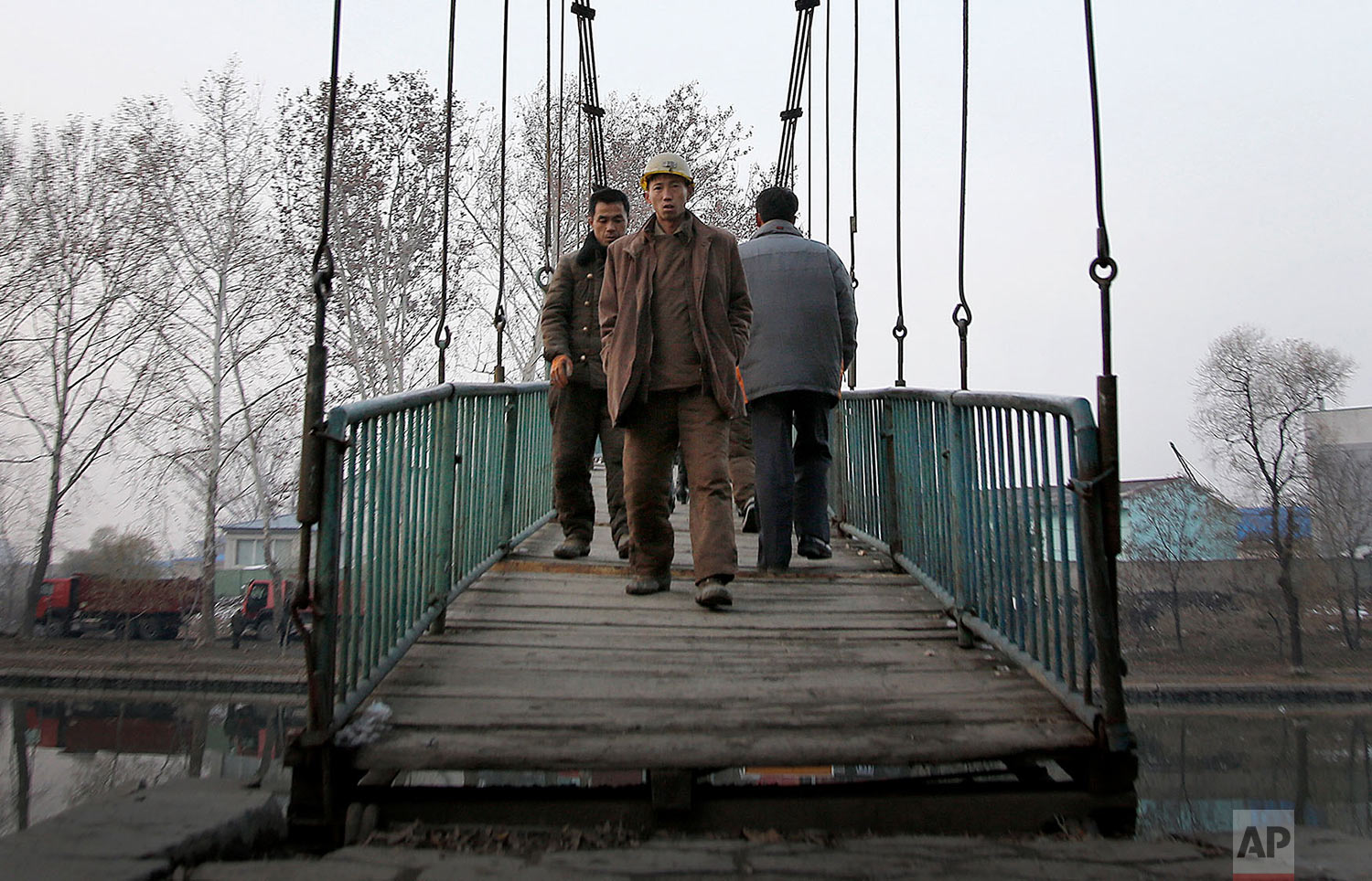 Construction workers walk on a bridge that takes them over the Pothong River in Pyongyang, North Korea, on Nov. 28, 2015. The Pothong River is the second largest river that runs through the North Korean capital. (AP Photo/Wong Maye-E)