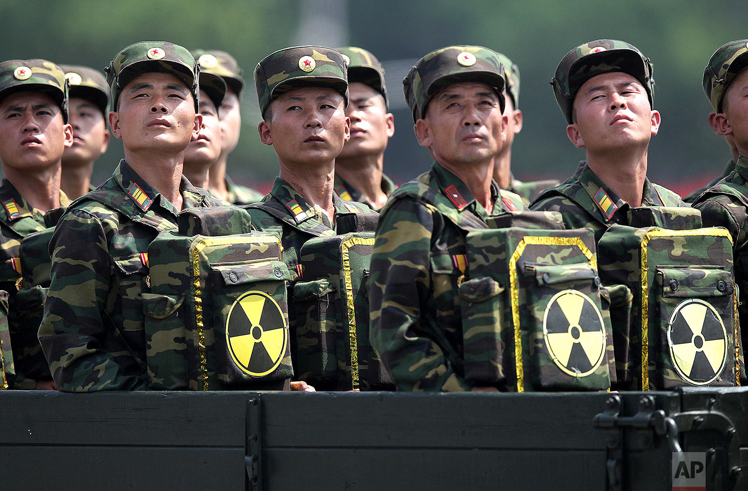 North Korean soldiers turn to look toward their leader, Kim Jong Un, as they carry packs marked with the nuclear symbol during a parade marking the 60th anniversary of the Korean War armistice in Pyongyang, North Korea, on July 27, 2013. (AP Photo/Wong Maye-E)