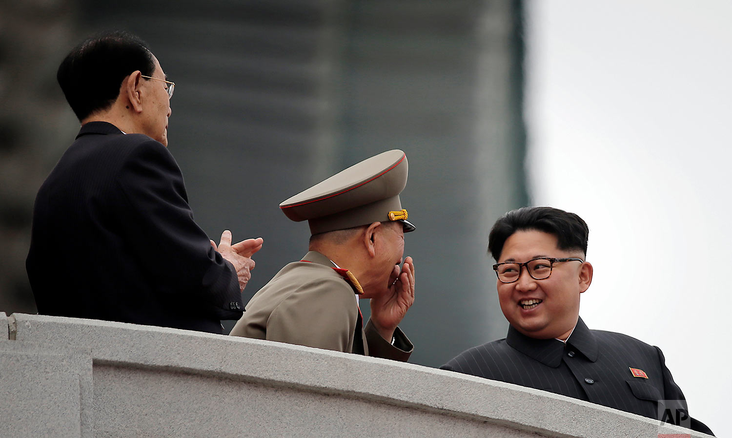North Korean leader Kim Jong Un, right, smiles at Hwang Pyong So, the top political officer of the Korean People's Army, center, and Kim Yong Nam, the head of North Korea's parliament, left, as they watch a parade at Kim Il Sung Square in Pyongyang, North Korea, on May 10, 2016. (AP Photo/Wong Maye-E)