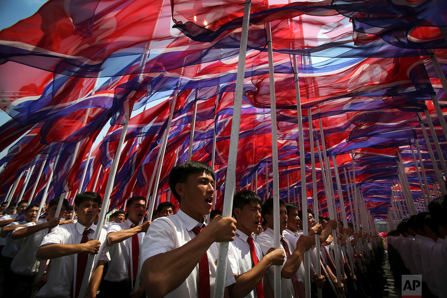 Men carrying North Korean flags march in a mass military parade in Pyongyang, North Korea, celebrating the 60th anniversary of the Korean War armistice on July 27, 2013. (AP Photo/Wong Maye-E)