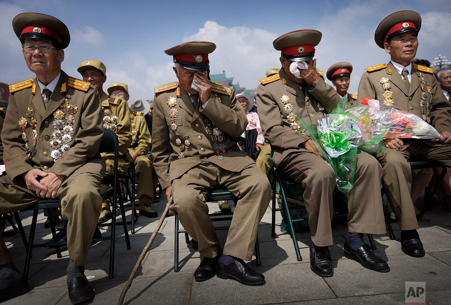 North Korean war veterans express varying degrees of emotion as they watch a parade in Pyongyang's Kim Il Sung Square on July 27, 2014, to mark the 61st anniversary of the armistice that halted fighting in the Korean War. (AP Photo/Wong Maye-E)