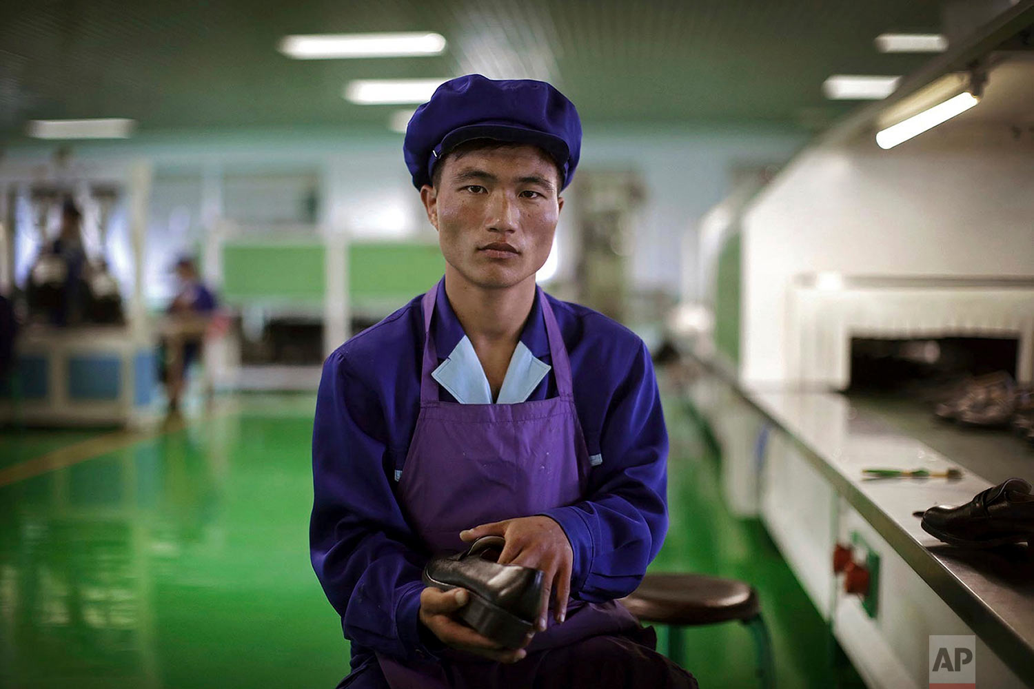 Kang Jong Jin, a 28-year old former soldier who attaches soles to shoes at a shoe factory in Wonsan, North Korea, poses for a portrait at his work station on June 22, 2016. (AP Photo/Wong Maye-E)