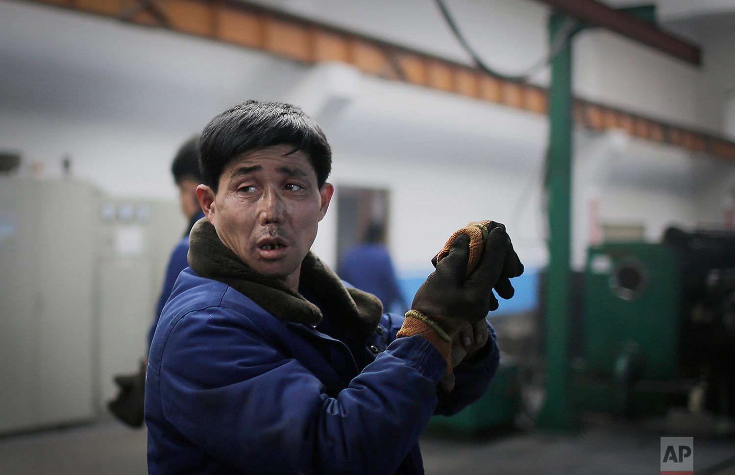 A factory worker takes off his gloves at the Pyongyang 326 Electric Wire Factory in Pyongyang, North Korea, on Jan. 10, 2017. (AP Photo/Wong Maye-E)