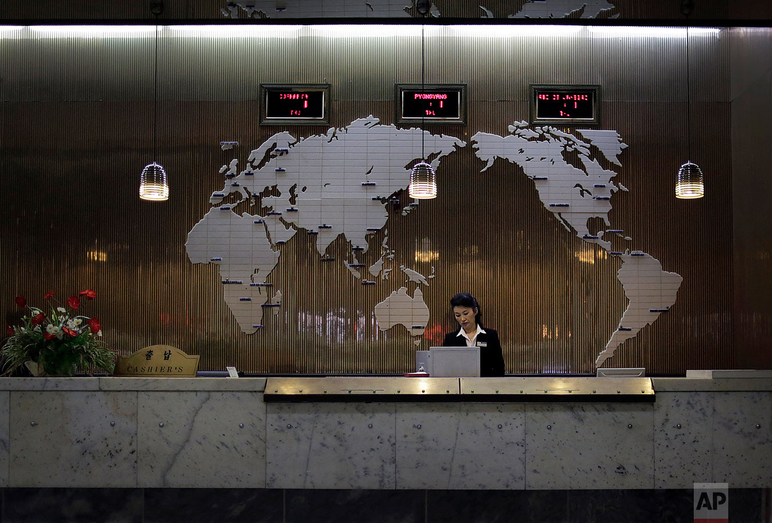 A hotel staff member stands at a reception desk decorated with a map of the world on Oct. 23, 2014, in Pyongyang, North Korea. (AP Photo/Wong Maye-E)