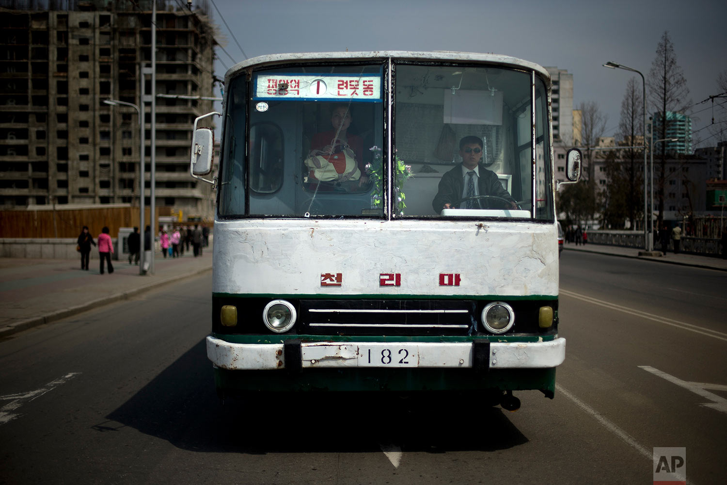 A man drives a bus while a woman looks out through the cracked windshield in Pyongyang, North Korea, on April 15, 2013. (AP Photo/Alexander F. Yuan)
