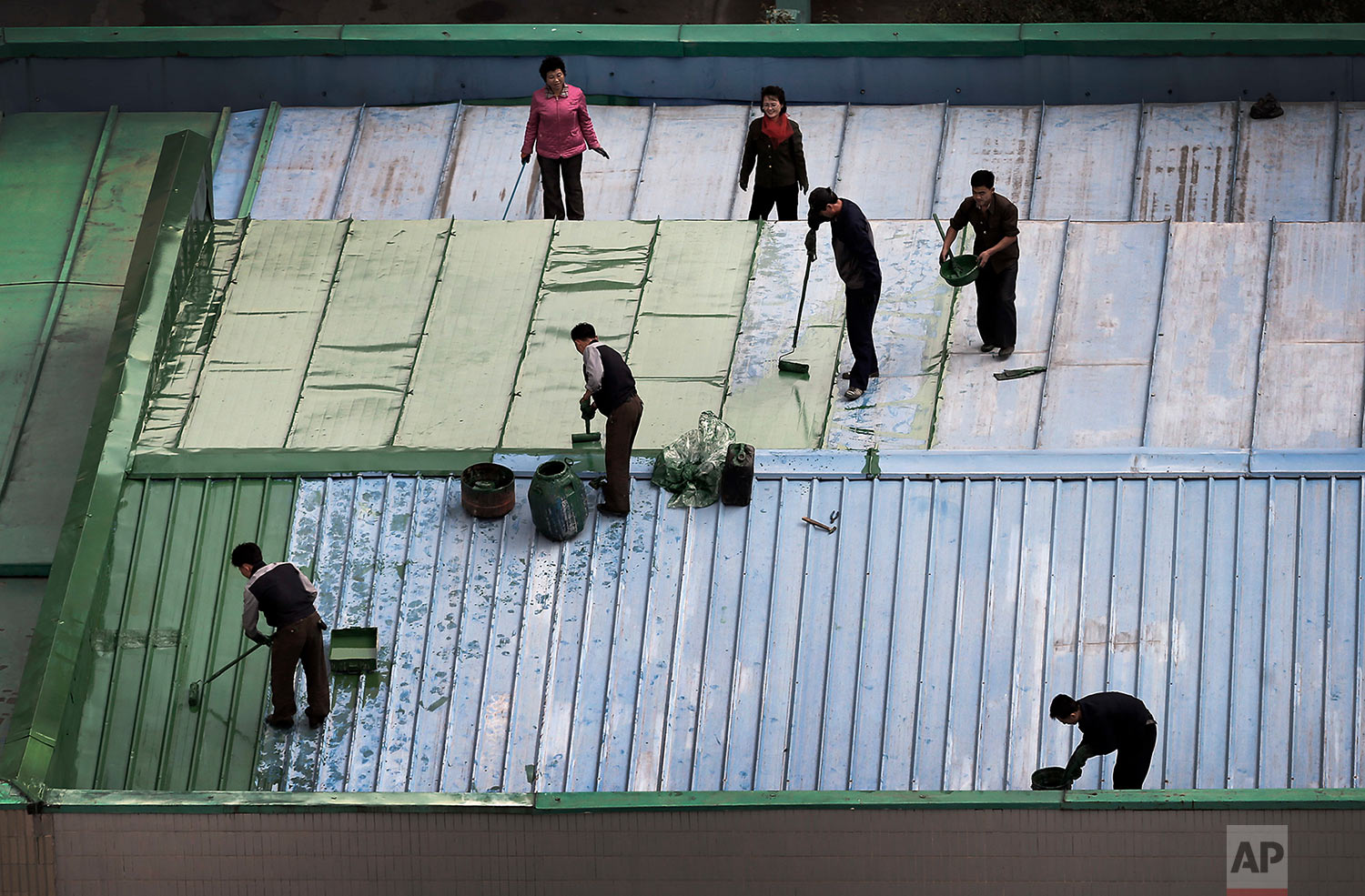 Men and woman paint the roof of a restaurant in downtown Pyongyang, North Korea, on Oct. 25, 2014. (AP Photo/Wong Maye-E)