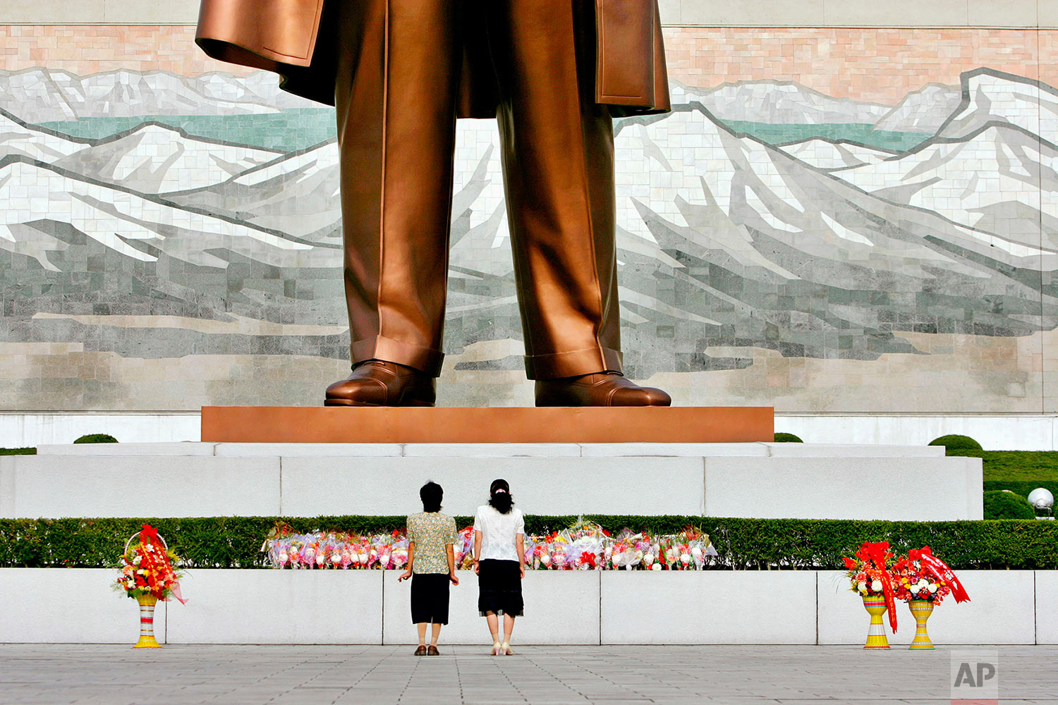 Women prepare to bow before the statue of late North Korean leader Kim Il Sung, erected on Mansu Hill in Pyongyang, North Korea, on Aug. 5, 2007. (AP Photo/Elizabeth Dalziel)