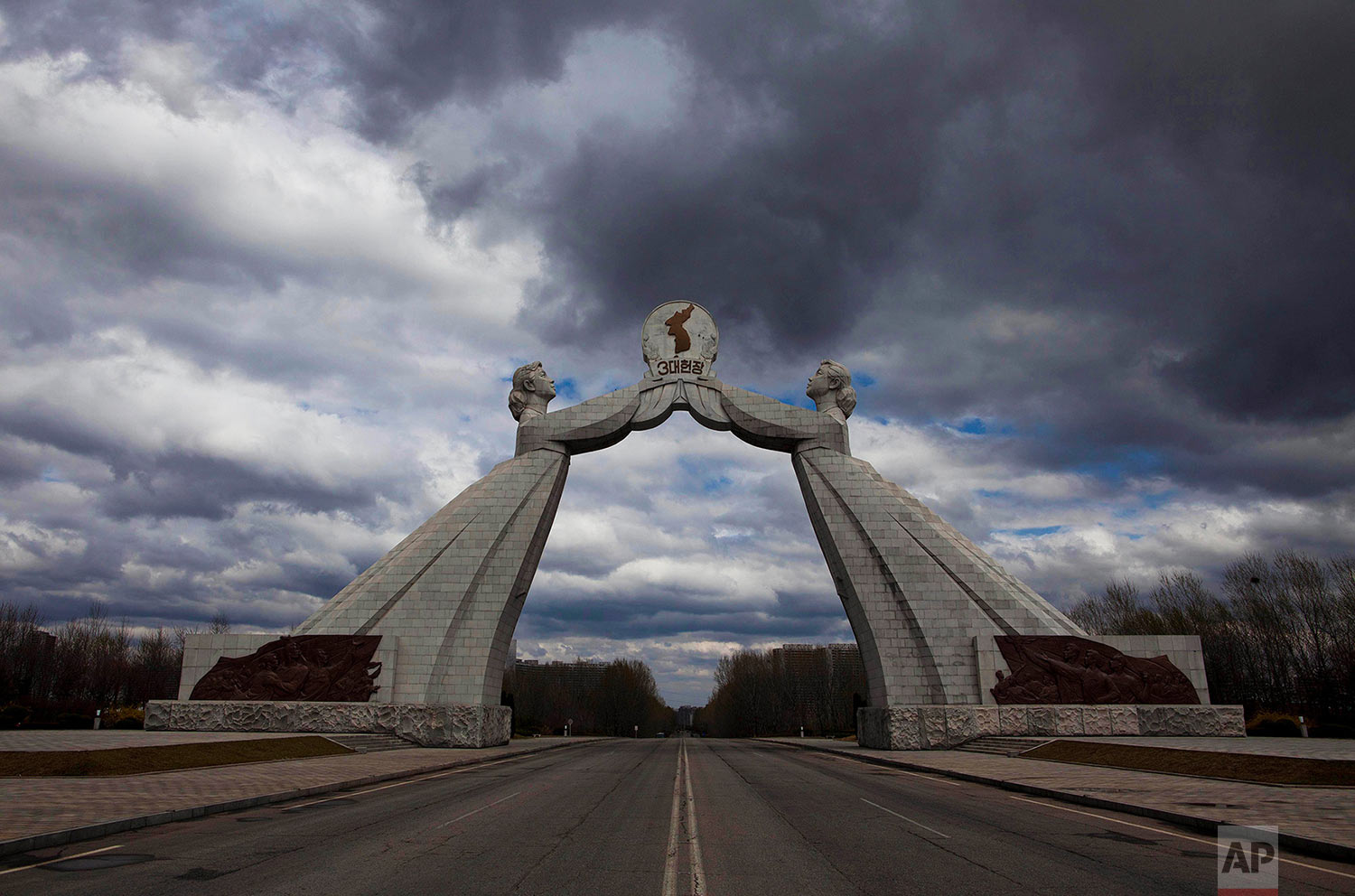 A statue known as the Monument to the Three Charters for National Reunification, which symbolizes the hope for eventual reunification of the two Koreas, arches over a highway at the edge of Pyongyang, North Korea, on April 18, 2011. (AP Photo/David Guttenfelder)