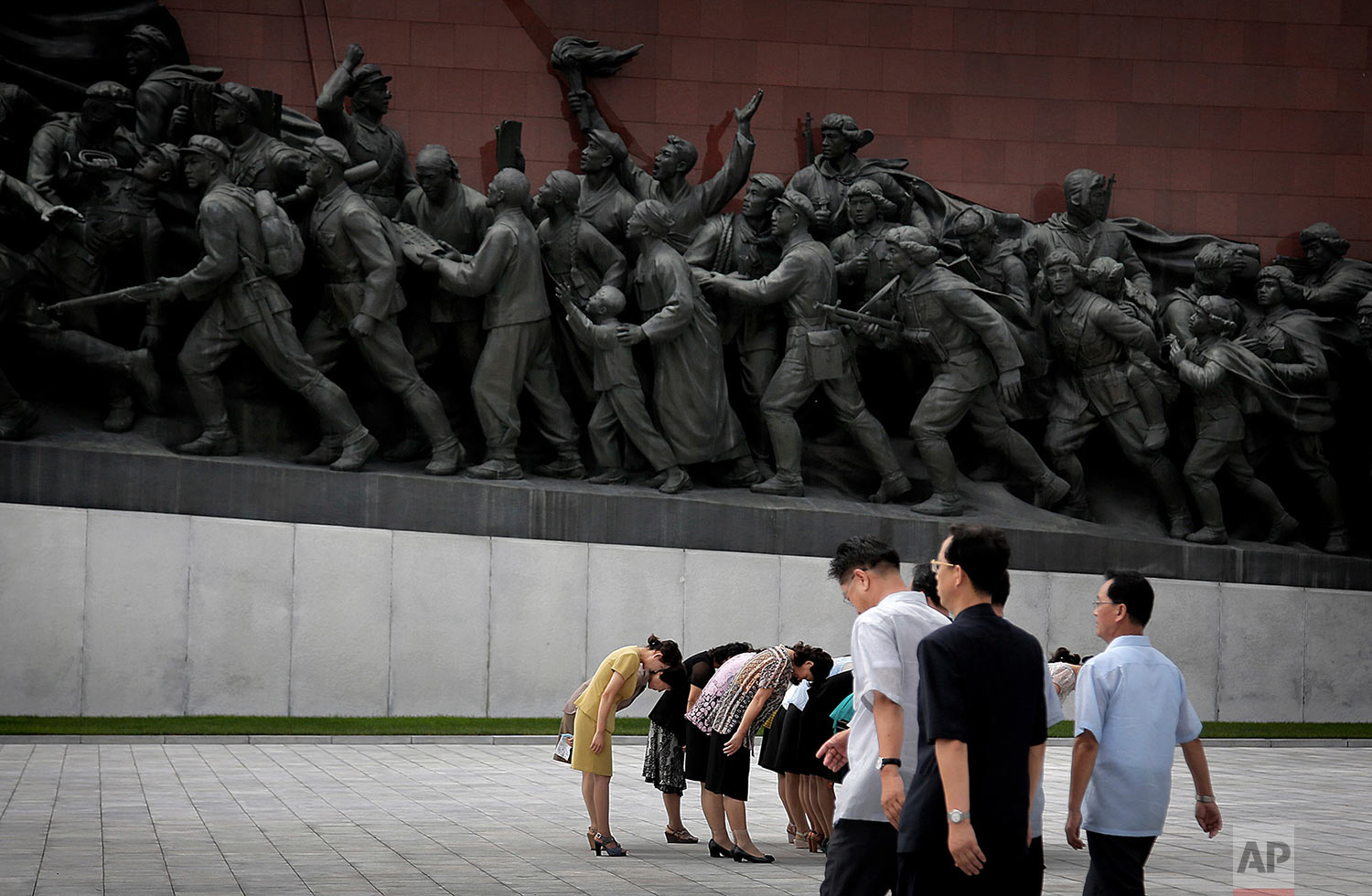 A group of women bow to bronze statues of the late leaders Kim Il Sung and Kim Jong Il at Munsu Hill in Pyongyang, North Korea, on July 27, 2015, amid celebrations to mark the 62nd anniversary of the armistice that halted the Korean War. (AP Photo/Wong Maye-E)