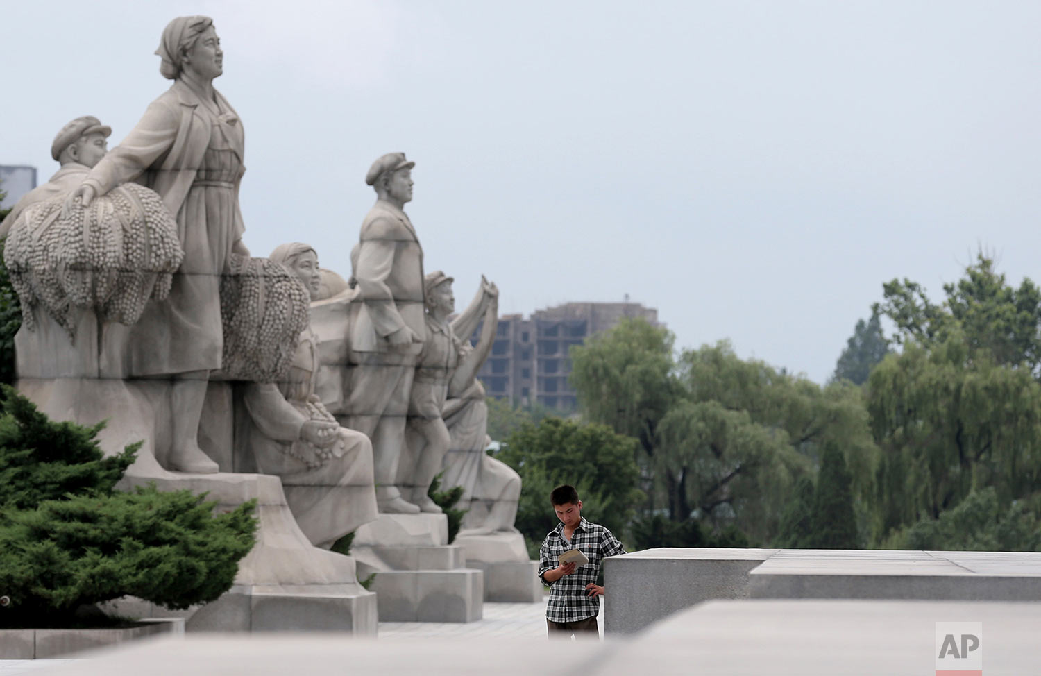 A young North Korean man stands reading next to statues at the Ju Che Tower in Pyongyang on July 21, 2013. (AP Photo/Wong Maye-E)
