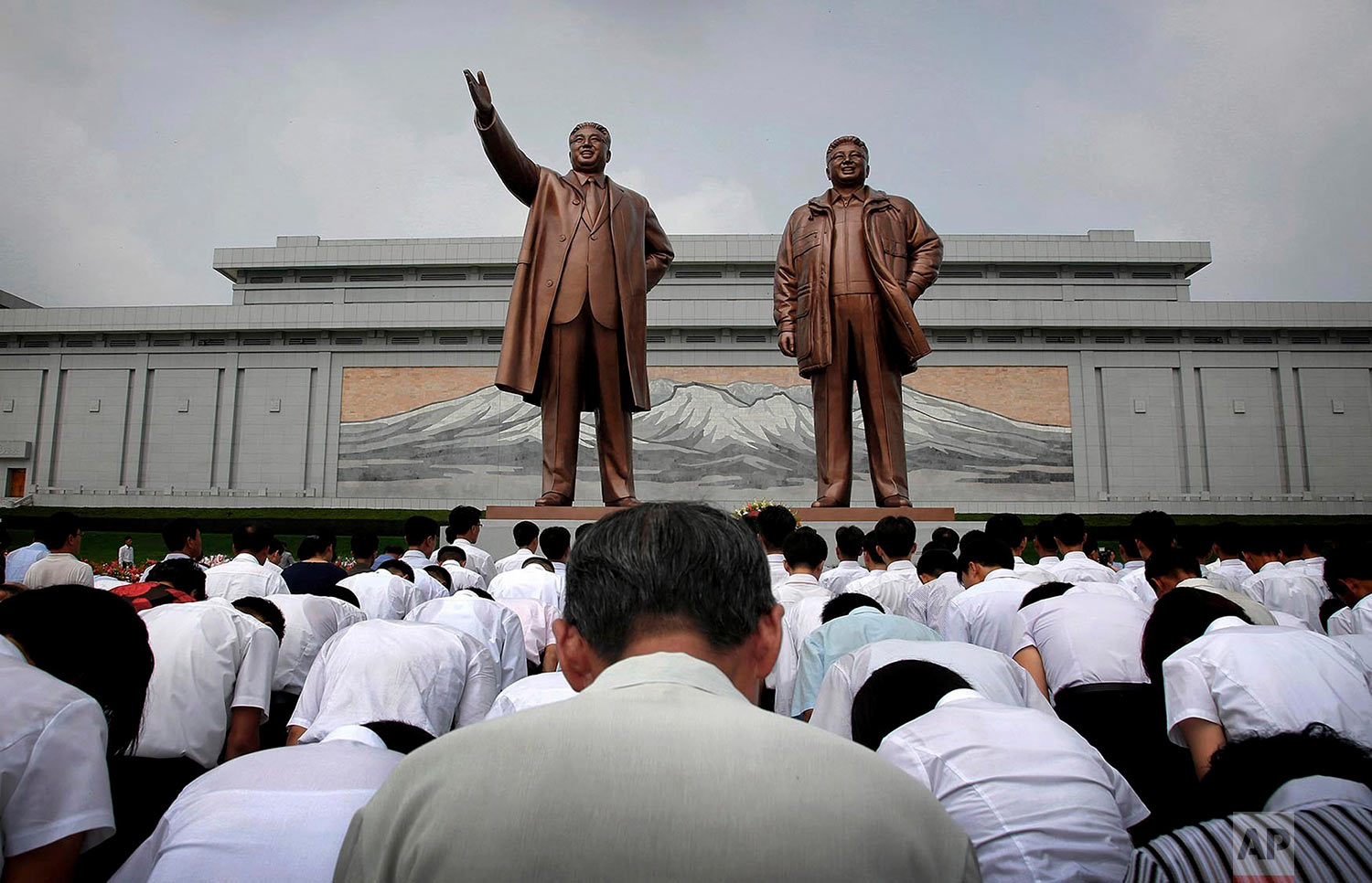 North Koreans bow in front of bronze statues of the late leaders Kim Il Sung, left, and Kim Jong Il at Munsu Hill in Pyongyang on July 27, 2015. The statues were created by artists from Mansudae Art Studio. Since its opening by Kim Il Sung in 1959, the studio has produced an estimated 38,000 statues and 170,000 other monuments for domestic use. (AP Photo/Wong Maye-E)
