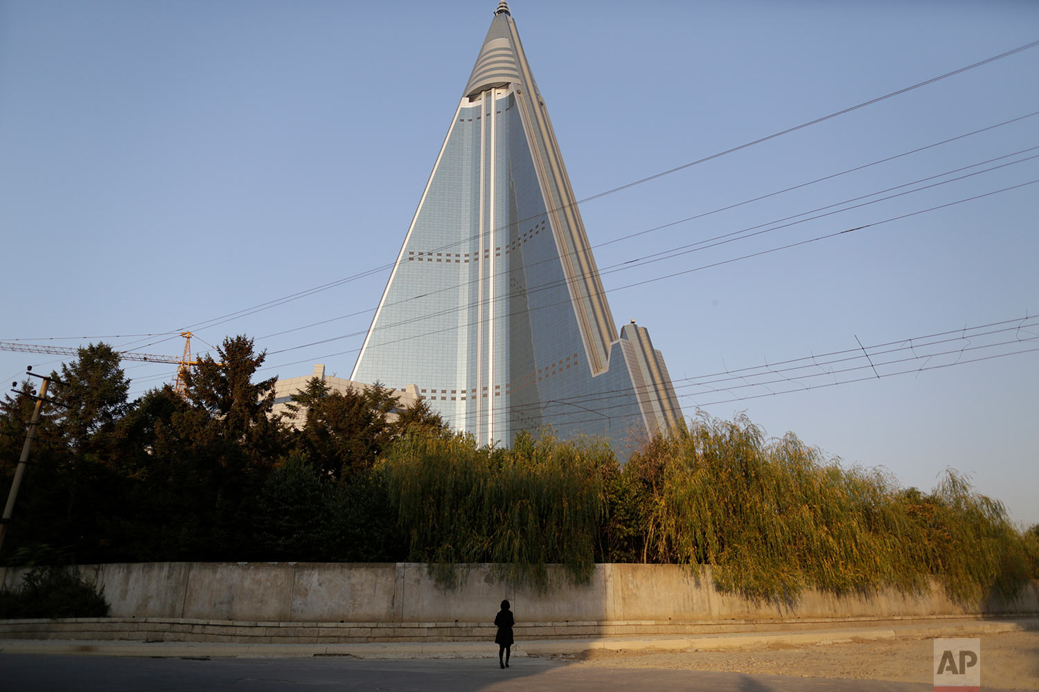 A woman walks near the 105-story Ryugyong Hotel in Pyongyang, North Korea, on Oct. 22, 2014. Construction on the massive hotel began in 1987, but the country's economic difficulties forced the project into repeated delays. Three decades later, the building has become a major Pyongyang landmark but has never been used as a hotel. (AP Photo/Wong Maye-E)