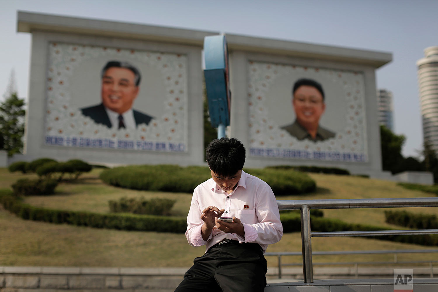 A man uses his smartphone in front of portraits of the late North Korean leaders Kim Il Sung, left, and Kim Jong Il in Pyongyang, North Korea, on May 5, 2015. North Koreans have gained greater access to media and devices like cellphones during Kim Jong Un's rule. (AP Photo/Wong Maye-E)