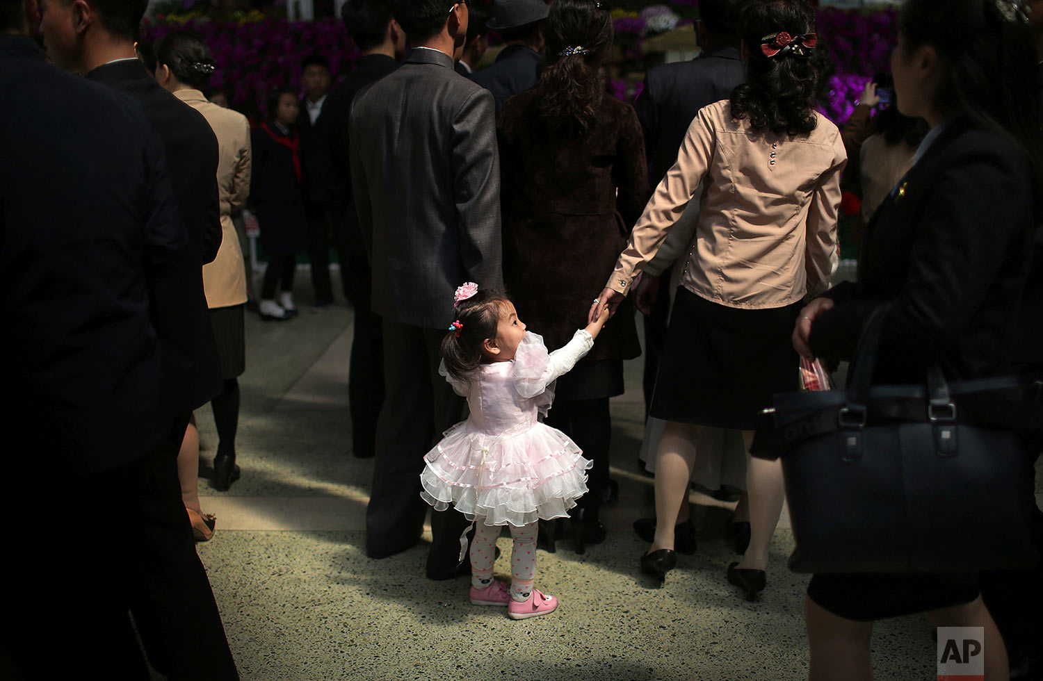 A family visits a flower festival during a celebration to mark the 105th anniversary of the birth of the late leader Kim Il Sung on April 16, 2017, in Pyongyang, North Korea. (AP Photo/Wong Maye-E)