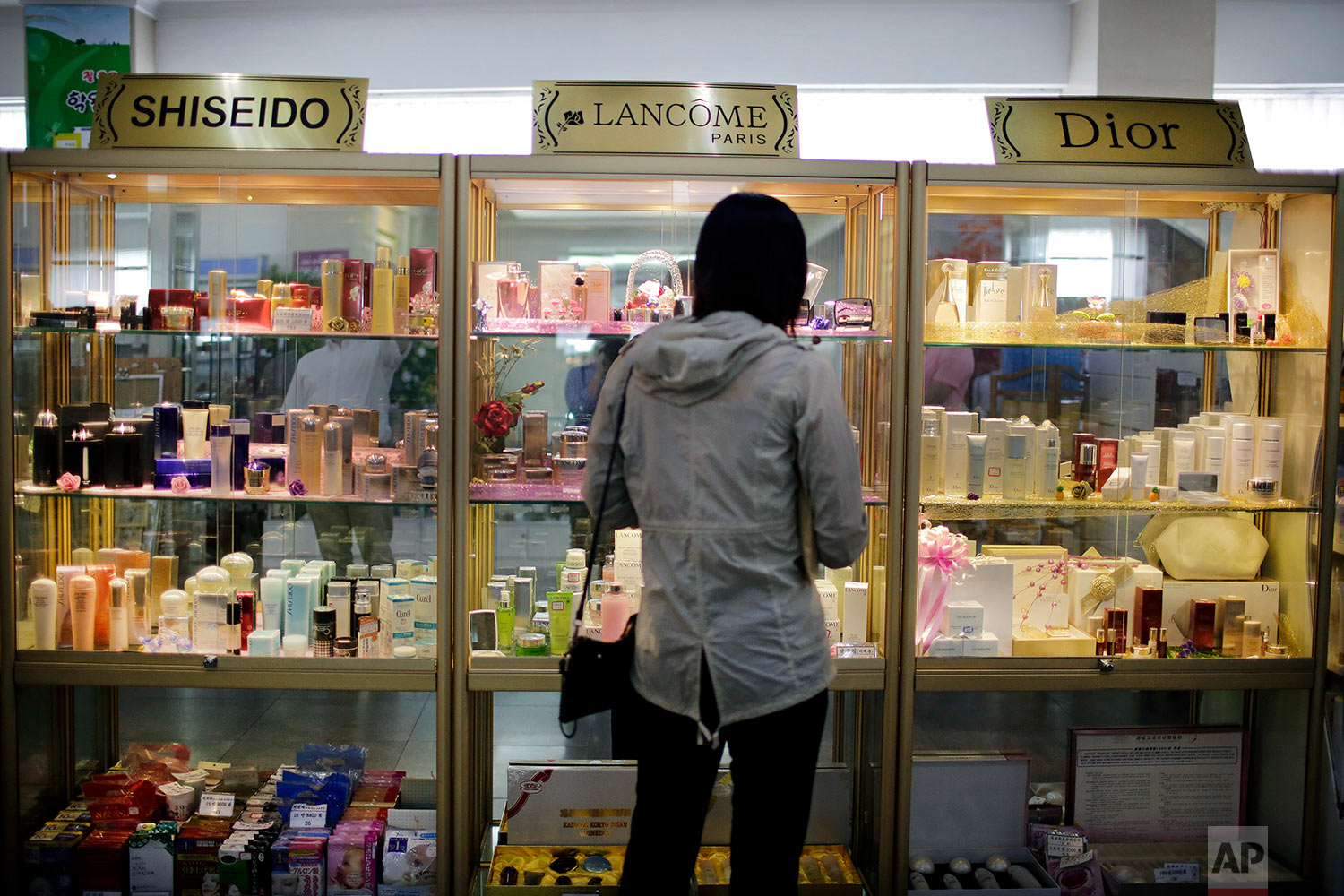A woman looks at a display of imported cosmetics and perfume on the second level of the upscale Potonggang department store in Pyongyang, North Korea. Three generations into the ruling dynasty founded by Kim Il Sung, markets have blossomed and a consumer culture is taking root. (AP Photo/Wong Maye-E)