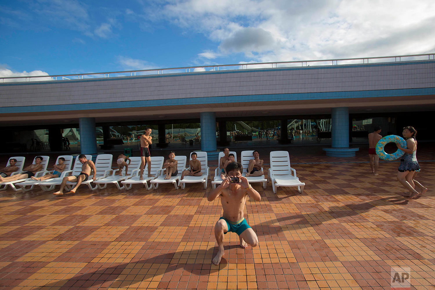 A man takes a photograph while his friends rest on deck chairs at a water slide and swimming pool complex in Pyongyang, North Korea, on Sept. 8, 2012. (AP Photo/David Guttenfelder)