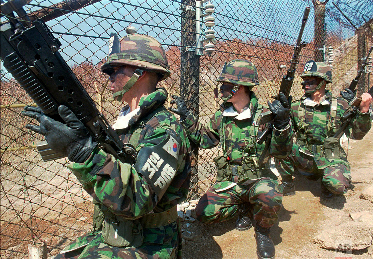South Korean soldiers take their position along the wire fence in the Demilitarized Zone separating the two Koreas near the truce village of Panmunjom on April 8, 1996, the day after armed North Korean troops marched into the DMZ. (AP Photo/Ahn Young-joon)