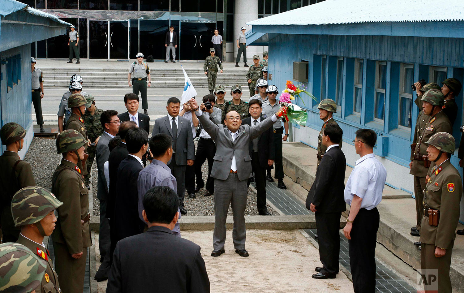 """Activist No Su-hui, center, shouts """"Long Live Reunification"""" in front of North Korean officials and soldiers, foreground, before crossing the demarcation line between North and South Korea where South Korean officials were waiting for him, at the Demilitarized Zone at Panmunjom, Korea, on July 5, 2012. South Korean officials immediately detained the activist for making an extended trip to Pyongyang without South Korean government approval as required by law. (AP Photo/Kim Kwang Hyon)"""