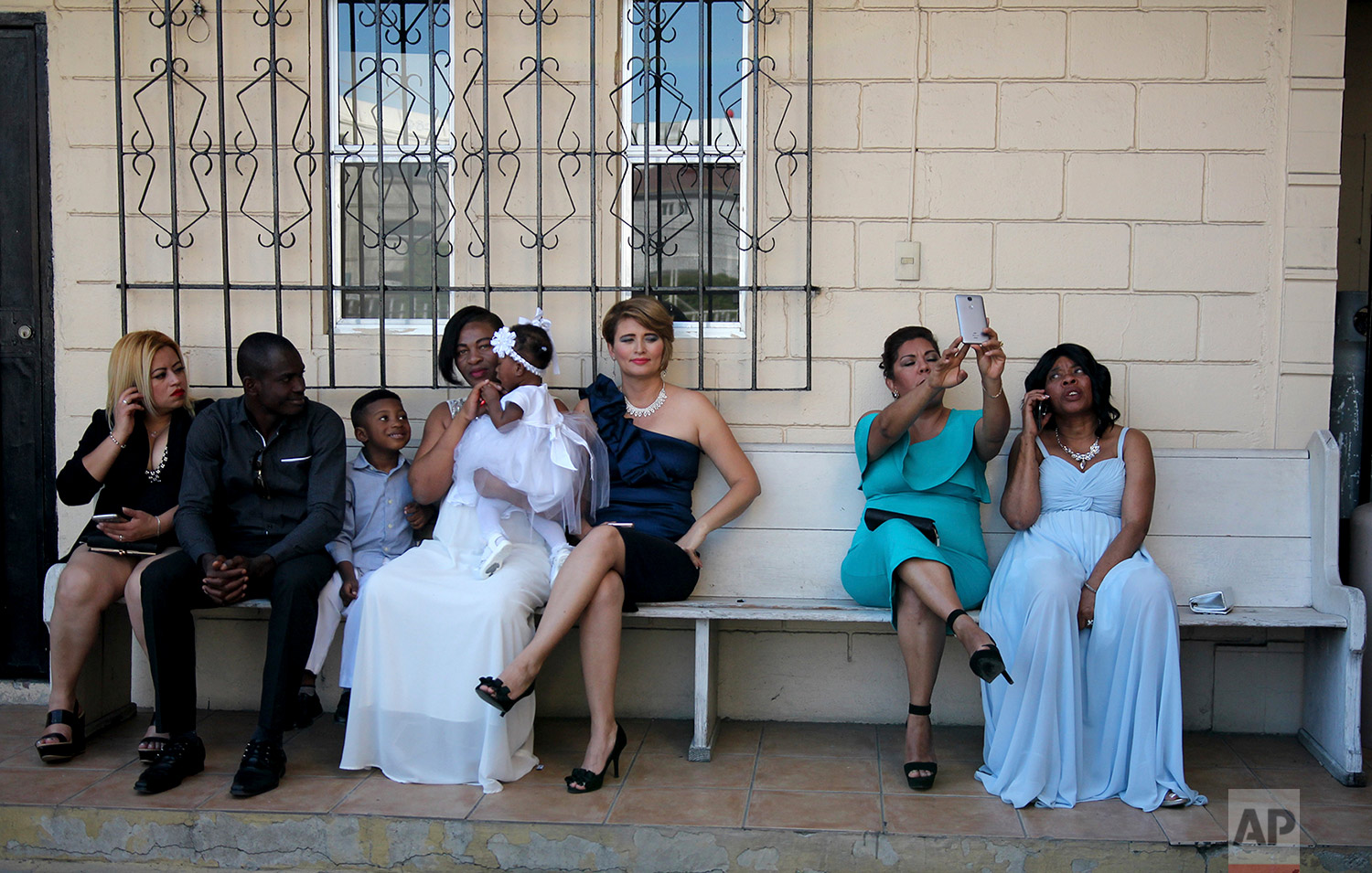 Brides and their guests sit on a bench in a parking lot prior to a mass wedding at the First Baptist Church of Tijuana, Mexico, May 5, 2018. (AP Photo/Emilio Espejel)