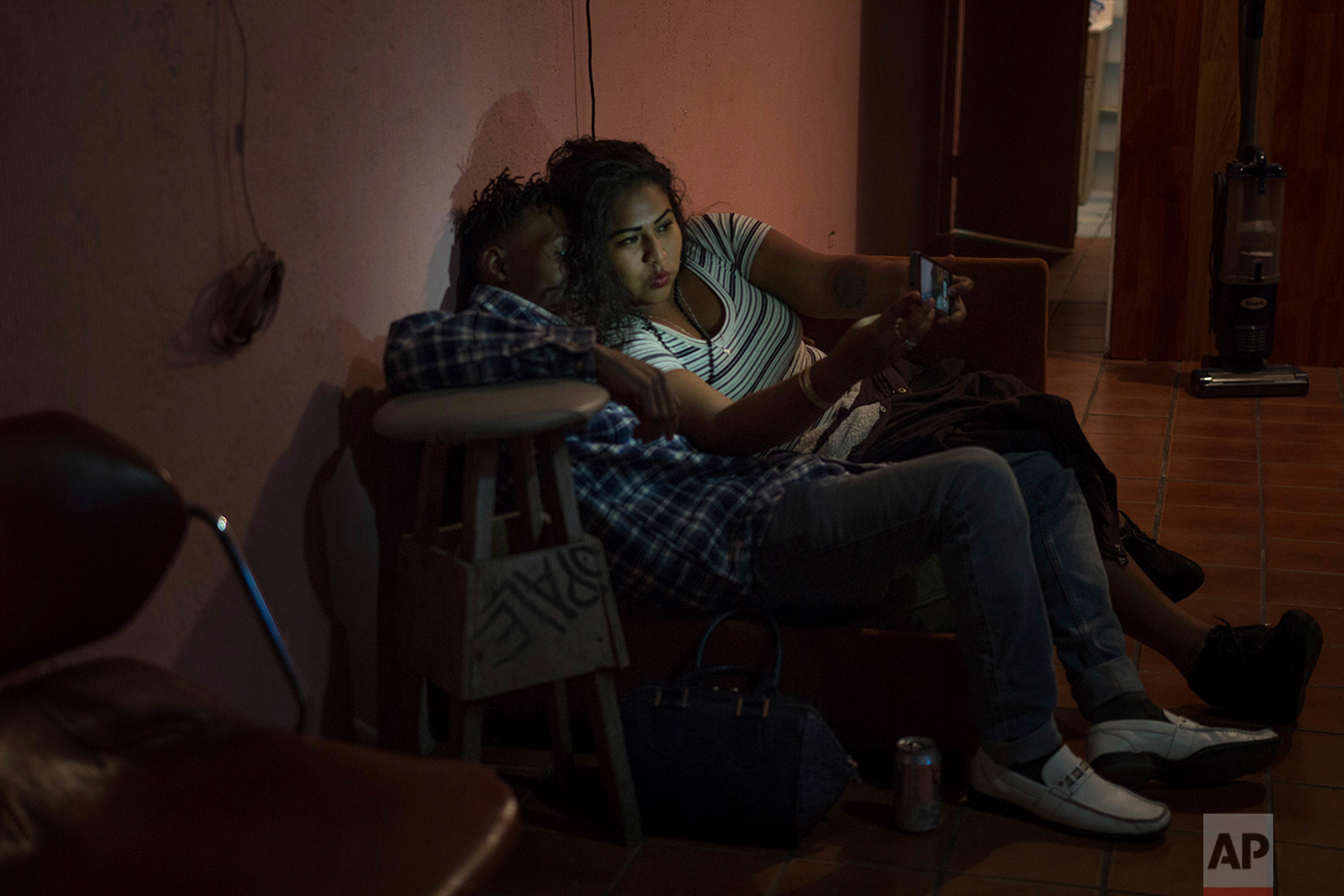 Adriana,from Mexico, and Etienne, from Haiti, take a selfie during a party in Tijuana, Mexico, Feb. 25, 2018. (AP Photo/Emilio Espejel)
