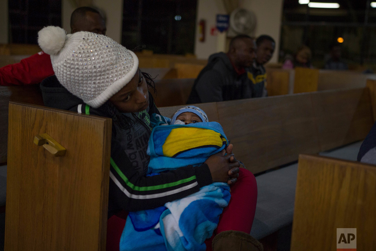 A woman holds her baby during a service at The First Baptist Church of Tijuana in Mexico, Feb. 26, 2018.The church is located in downtown Tijuana and forms an important part of Haitian community life in the city. (AP Photo/Emilio Espejel)