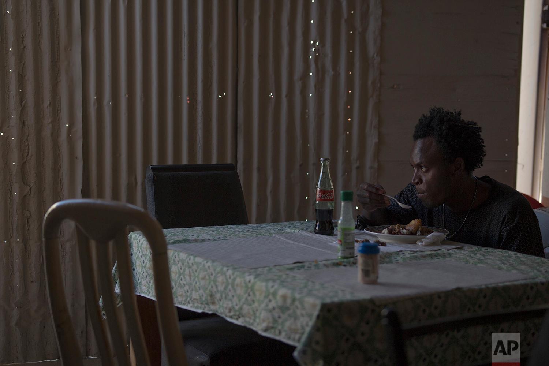 A man eats chicken with rice at Yolanda's Haitian restaurant in Tijuana, Mexico, Feb. 20, 2018.Yolanda runs the restaurant with her husband and a partner.(AP Photo/Emilio Espejel)