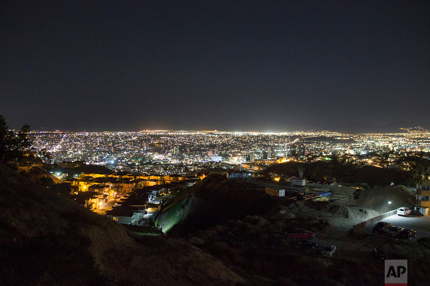Lights shine over the city of Tijuana, Mexico, Feb. 21, 2018. San Diego's office towers can be seen in the distance. (AP Photo/Emilio Espejel)