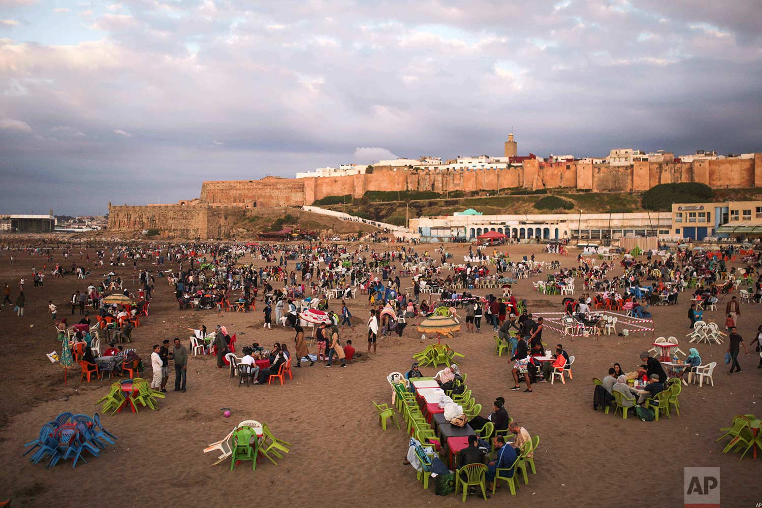 People gather on the beach before sunset to break their fast in the holy month of Ramadan, Rabat, Morocco, Saturday, June 9, 2018. (AP Photo/Mosa'ab Elshamy)